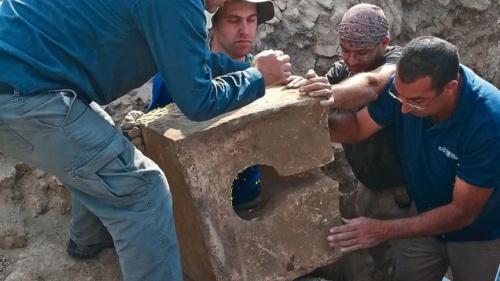 Les ouvriers enlèvent le siège d'une toilette en pierre utilisée pour désacraliser le sanctuaire lorsque l'autel fut découvert.