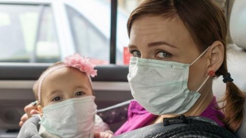 Une mère et son bébé qui portent des masques