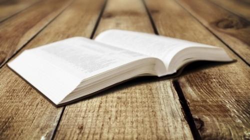 Une Bible ouverte posée sur une table.