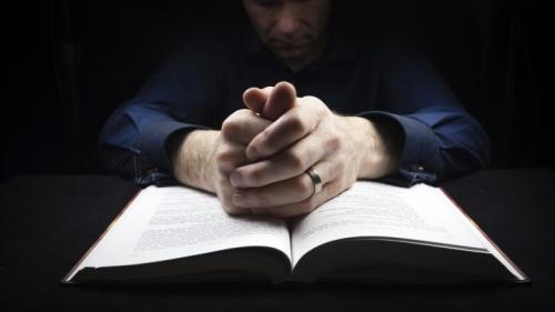 Un homme qui prie avec sa Bible