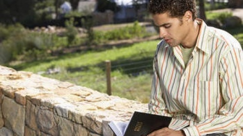 Un jeune homme lisant la Bible.