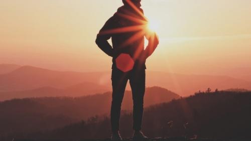 La silhouette d'un homme avec des montagnes à l'arrière-plan