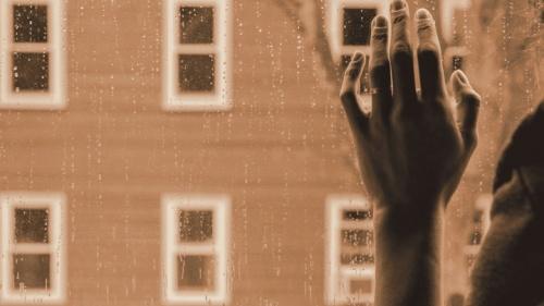 Une personne regarde la pluie par la fenêtre