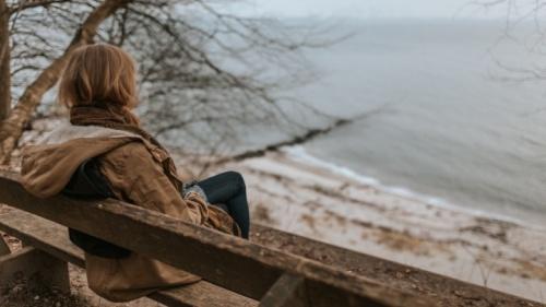 Une femme assise près d'un lac