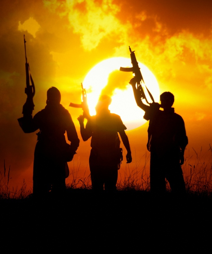 Trois hommes tenant des mitraillettes en l'air.
