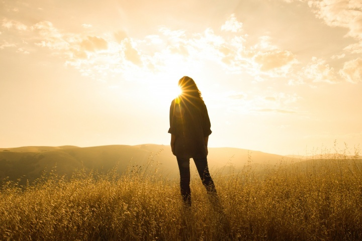 Une femme dans un champs qui regard le soleil au-dessous des montagnes