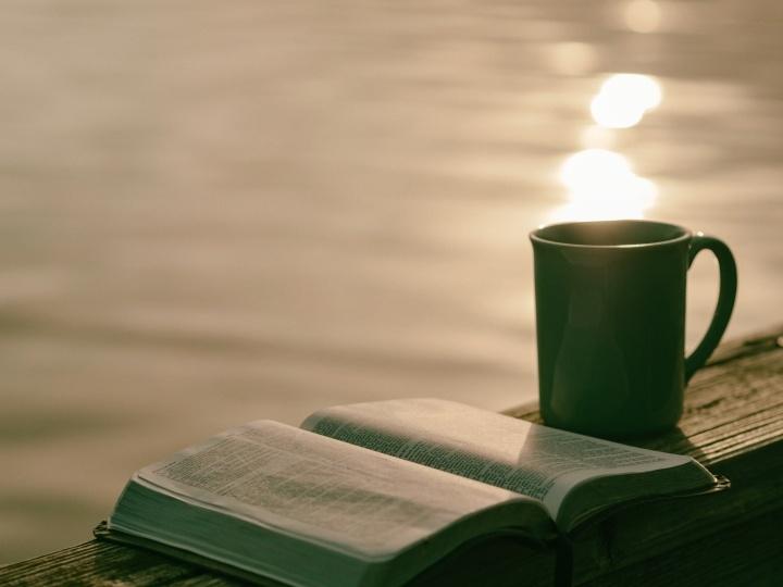 Une Bible est une tasse au bord de l'eau