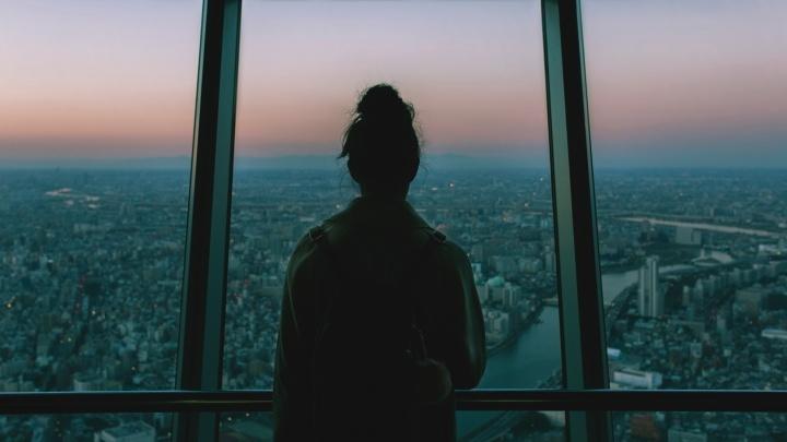 Une fille qui regarde une grande ville par la fenêtre au crépuscule