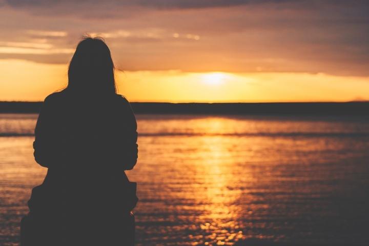 La silhouette d'une femme qui regarde un coucher de soleil sur l'océan