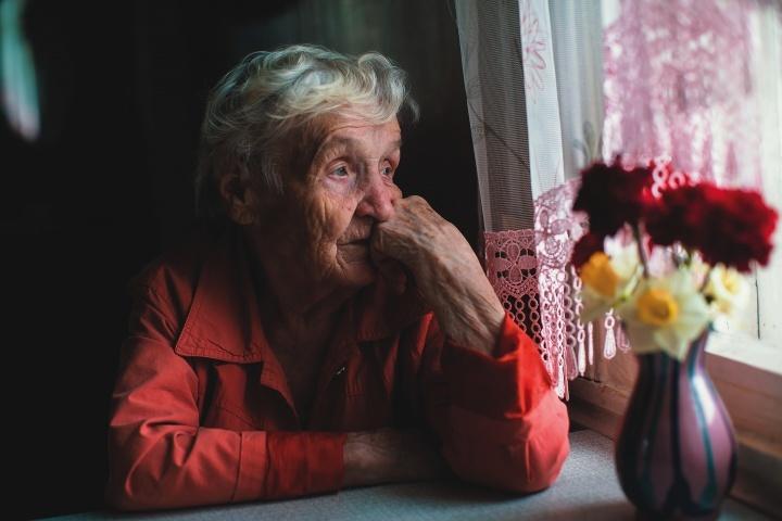 Une vieille dame regarde par la fenêtre