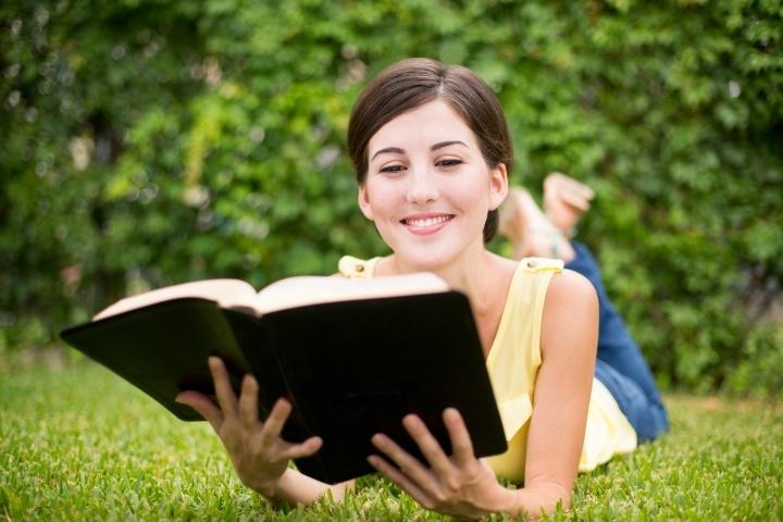 Une femme souriante lit la Bible
